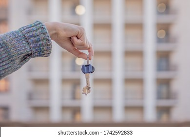 keys in hand, hand holds the keys to the apartment on the background of a new house. The concept of buying, selling, renting. Real estate agency, sale transaction