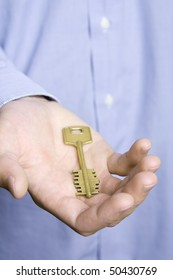 Keys to the house in the palm of a young man in a blue shirt