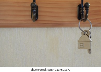 Keys with house shaped keychain hanging on hook on light yellow wall background with copy space for text. Real estate, buying and moving new home or renting property concept.