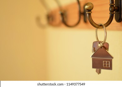Keys with house shaped keychain hanging on hook on yellow blurred wall background with copy space for text at shallow depth of field. Real estate, buying and moving new home or renting property concep