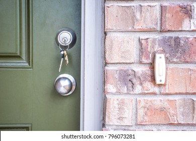Keys inside front door Deadbolt of new Brick Home. Door bell and green front door.