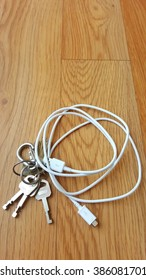 keys and mobile cable  on wood floor do not forget it before go out.
