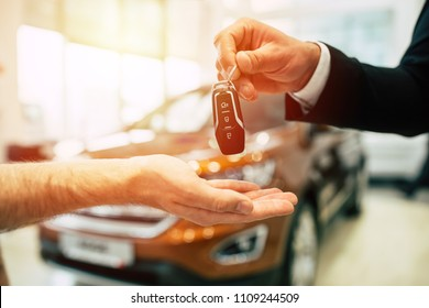 Keys from new car, young salesman transfer the car key in hand of customer in casual wear on dealership background
