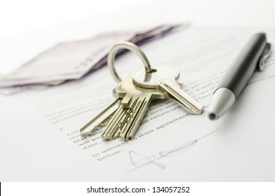 Keys of a new house on a signed contract of house sale with money in background. Concept of closed deal.