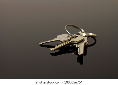Keys on a black reflecting surface background closeup