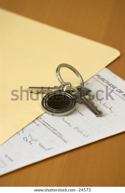 Keys on manilla folder, legal document visible, on wooden desk top.
