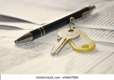 Keys on a signed contract of house sale and pen