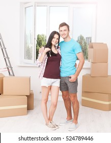 Keys of their new house. Cheerful young couple holding keys and smiling while standing in their new house
