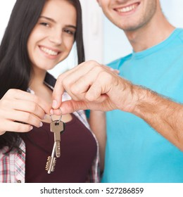 Keys of their new house. Cheerful young couple man and woman holding keys and smiling while standing in their new house