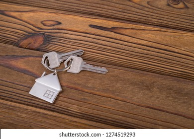 Keys with trinket house on wood background. The concept of buying a new home, mortgage, loan, court