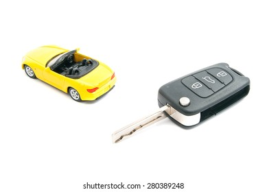 keys and yellow sport car on white closeup