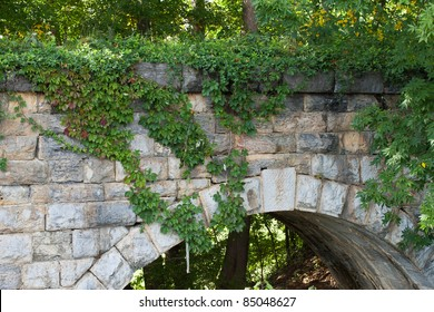 Keystone view of old stone bridge built in 1874 with close up of Virginia Creeper