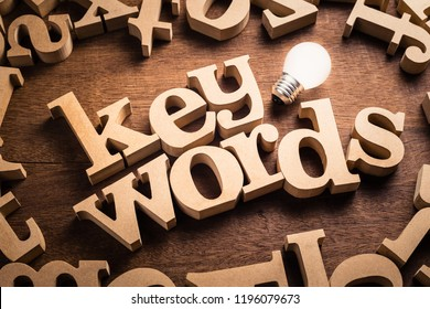 Keyword word in scattered wood letters with glowing white light bulb