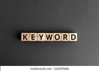 Keyword - word from wooden blocks with letters, search information that contains that word keyword concept, random letters around, white  background