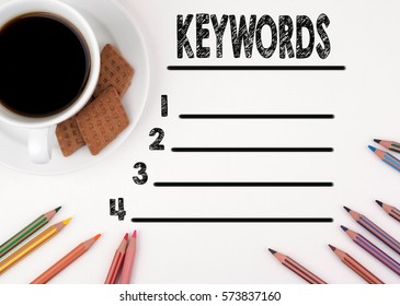 Keywords blank list. White desk with a pencil and a cup of coffee.