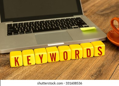 Keywords written on a wooden cube in front of a laptop