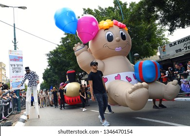 Kfar Saba, ISRAEL, MARCH 22: Baby balloon with acrobats and dressed up people are dancing and celebrating the Adloyada parade (traditional parade of Purim) near Tel Aviv, Israel, March 22, 2019