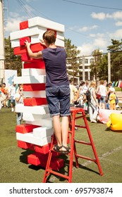 Khabarovsk, Russia - August 13, 2017: Young man play giant jenga game outdoors using a ladder. Person building a big tower of red and white bricks popular toy. Skills, choices and risk concept