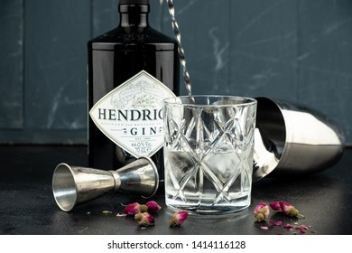 Khabarovsk, Russia - Jun 02, 2019: 70 cl bottle Hendricks distilled gin with glass and ice on dark rustic background. Lay next to the shaker and malenikie pink roses.