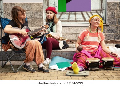 Khabarovsk, Russia - June 24, 2017: 3 cheerful street musicians playing music on a sidewalk. Three fun ladies performing a concert on musical instruments: guitar, drums and saxophone