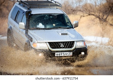 KHABAROVSK, RUSSIA - MARCH 25, 2017: Mitsubishi Pajero Sport on dirt road in early spring making splashes from a big puddle