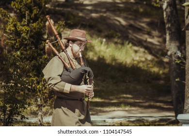 KHABAROVSK, RUSSIA - May 2018: Bagpipe player street musician in ethnic dress playing folk music