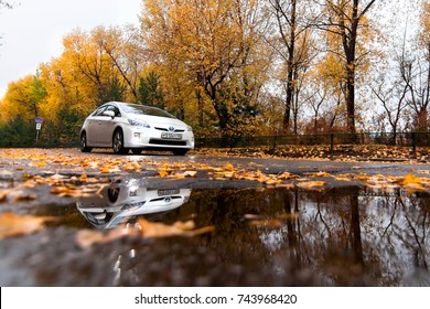 KHABAROVSK, RUSSIA - OCTOBER 14, 2017: White Toyota Prius on autumn road in rainy day