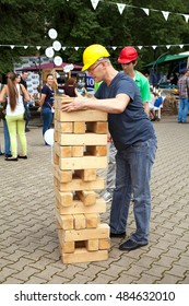 Khabarovsk, Russia - September 4, 2016: Contractor man playing game outdoors. Big, large, giant jenga competition