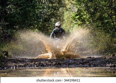 "KHABAROVSK RUSSIAN - SEPTEMBER 12 : racer in action at The  stage of the Khabarovsk enduro ""Drive trofy on September 12, 2015 in Khabarovsk Russia"" enduro rides through the mud with big splash"