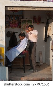 KHAJURAHO, INDIA - DEC 21, 2014: UnidentifiedIndian professional hairdresser in street salon. Khajuraho is small town with  Khajuraho Group of Monuments located in the Indian state of Madhya Pradesh