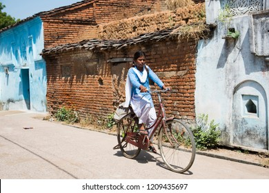 KHAJURAHO, MADHYA PRADESH, INDIA 9 OCTOBER 2018 : Unidentified Happy Indian rural school student going to school on the bicycle from their village to urban area for education.