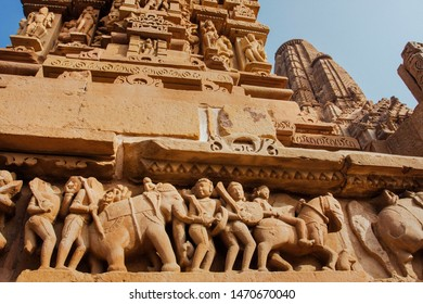 Khajuraho temple reliefs, India. Artworks on walls of 10th century temple with animals, wariors, horseriders. UNESCO Heritage site.