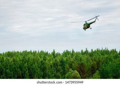Khaki colored helicopter is flying in blue sky above forest