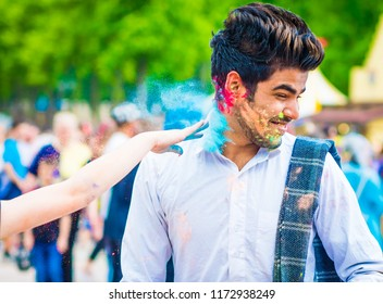 Khakiv, Ukraine - 19 May 2018: People sprinkle colorful paints during the festival. People with colorful faces celebrating holi fest