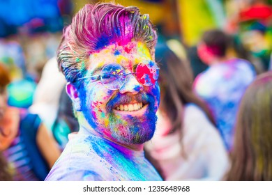 Khakiv, Ukraine - 19 May 2018: Portrait of smiling young man in glasses with colorful holi powder on his face. Holi color fest celebrating