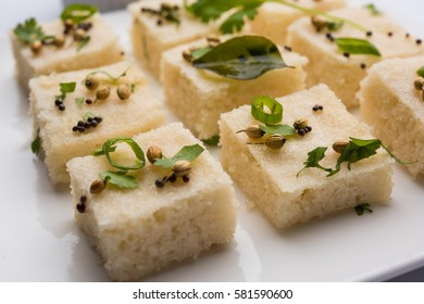 Khaman white Dhokla made up of rice or urad dal is a popular breakfast or Snacks recipe from Gujrat, India, served with Green chutney and hot tea. Selective focus