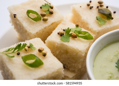 Khaman white Dhokla made up of rice or urad dal is a popular breakfast or Snacks recipe from Gujarat, India, served with Green chutney and hot tea. Selective focus