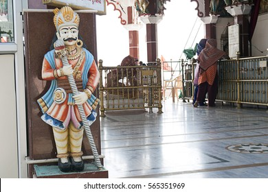 KHAMBHAT, GUJARAT / INDIA - JANUARY 11, 2017 : THE STATUE OF A GATEKEEPER AT THE ENTRANCE OF THE TEMPLE OF GODDESS SIKOTARA MAATA AND THE WOMEN ARE INSIDE THE TEMPLE WORSHIPING GODDESS, IN KHAMBHAT.