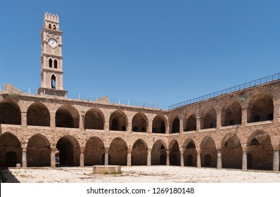 the khan al umdan caravanserai in acre akko israel showing the courtyard and clock tower with a clear blue sky