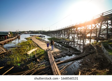 KHANCHANABURI,THAILAND-DECEMBER 4,2019: Long wooden Mon bridge destroyed and damaged by stream of strong flood with temporary wooden bridge in Sangkhlaburi of Kanchanaburi, Thailand
