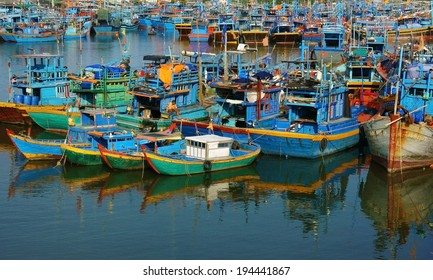 KHANH HOA, VIET NAM- JAN 20: Group of fishing boat anchor at harbor, wooden, colorful vessel reflect on water, this seaport support for fishery, VietNam, Jan 20, 2014