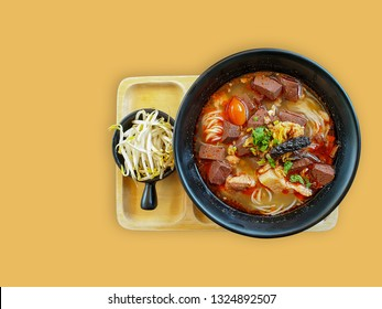 Khanom Jin Nam Ngiao or rice noodles with spicy chicken sauce on yellow background with clipping path.Bowl of spicy noodle soup, northern of thailand style cuisine (Khanom Jin Nam Ngiao)