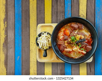 Khanom Jin Nam Ngiao or rice noodles with spicy chicken sauce on a wooden background with clipping path.Bowl of spicy noodle soup, northern of thailand style cuisine (Khanom Jin Nam Ngiao)
