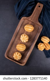 Khanom Khai or mini castella cake a Thai oval sweetmeat made with egg and sugar, soft dough on dark textured background, flat lay with selective focus