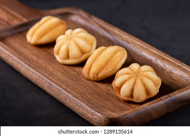 Khanom Khai or mini castella cake a Thai oval sweetmeat made with egg and sugar, soft dough on dark textured background with selective focus