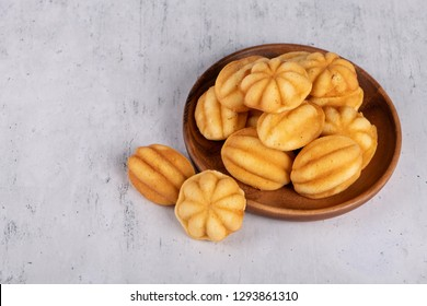 Khanom Khai or mini castella cake a Thai oval sweetmeat made with egg and sugar, soft dough on  wooden plate with selective focus