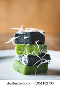 KHANOM PIAK POON, Black and Green Thai coconut milk sweet pudding with coconut shreds on top. Color from pandan leaf and charred coconut coir. Tower of dessert on white plate.
