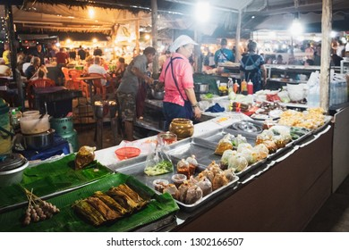 Khao Lak, Thailand - January 31, 2018: Thai woman selling spicy traditional Thai food at night market in Khao Lak, Thailand. Street cooking is a tradition and ubiquitous in Thailand.