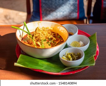 Khao Soi Kai Curry Noodles Soup with Chicken Northern Food Thailand style decorate with fried chili peppers and crispy fried egg noodles on side dish vegetable side view