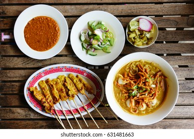 Khao soi and pork satay on wooden table. Khao soi is a northern food of Thailand